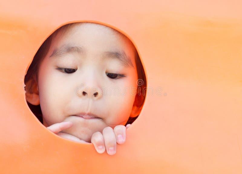 asiatisches Mädchen, das aus Plastikloch heraus schaut stockfotografie