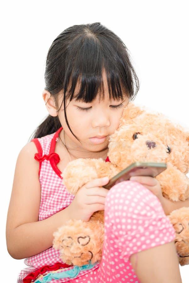 Asiatisches Mädchen, das den Smartphone lokalisiert spielt lizenzfreies stockbild