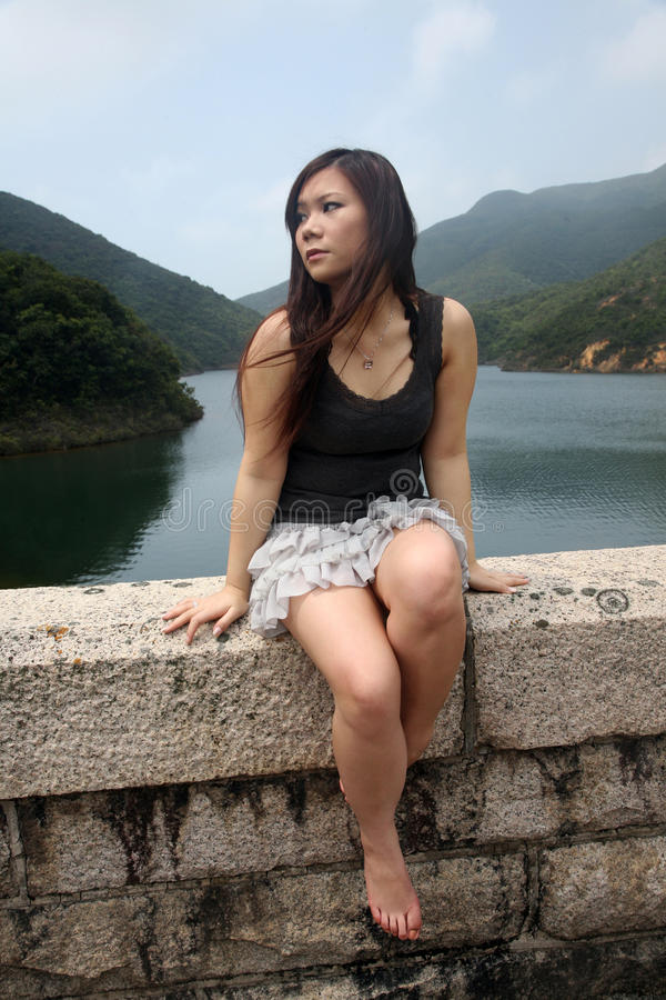 Asiatisches Mädchen, das draußen sitzt lizenzfreies stockfoto