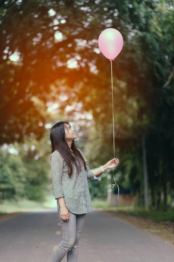 Asiatisches Mädchen, das einen Ballon im Park hält lizenzfreie stockbilder