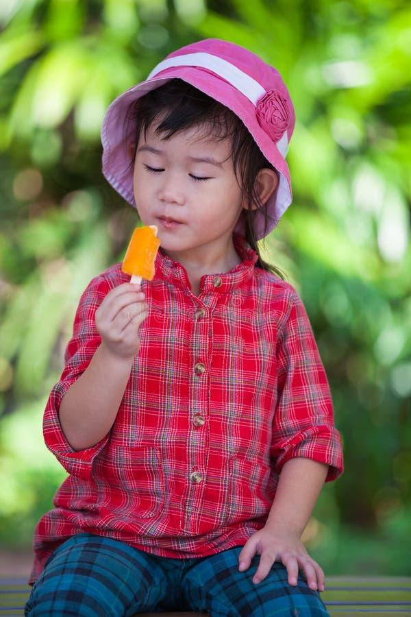 Asiatisches Mädchen, das Eiscreme im Sommer auf unscharfer Naturrückseite isst lizenzfreies stockfoto