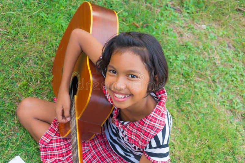 Asiatisches Mädchen, das Gitarre mit dem Lächeln auf ihrem Gesicht im grünen natu spielt stockfotografie