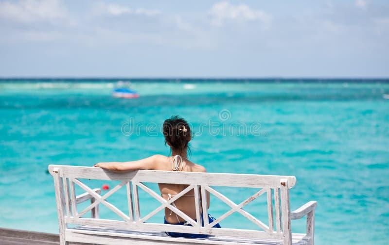 Asiatisches Mädchen, das im Stuhl überwacht das Meer sitzt lizenzfreie stockbilder