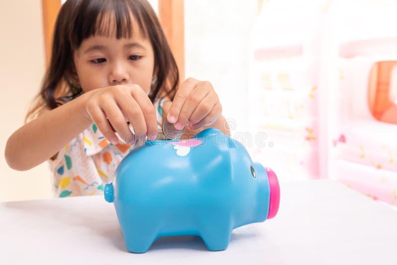 Asiatisches Mädchen, das Münze in das Sparschwein für Rettungsgeld einsetzt Selektiver Fokus der Kinderhand lizenzfreie stockfotografie