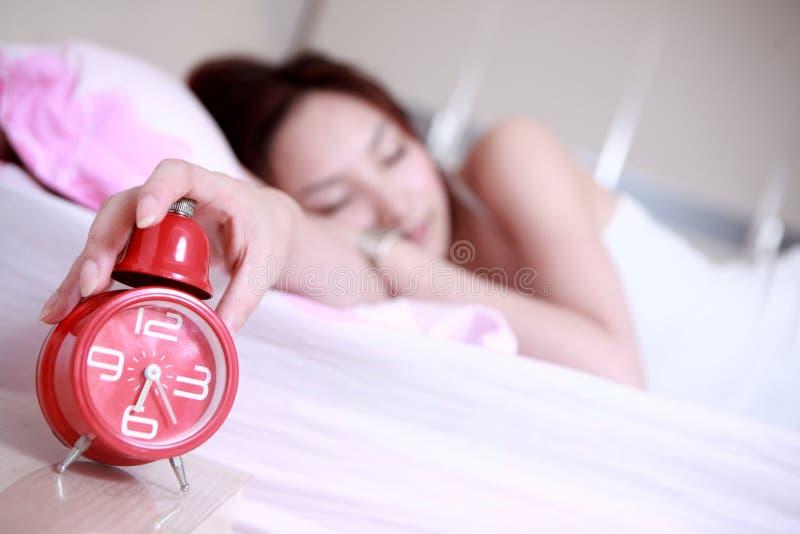 Asiatisches Mädchen, das mit Borduhr schläft lizenzfreie stockfotos