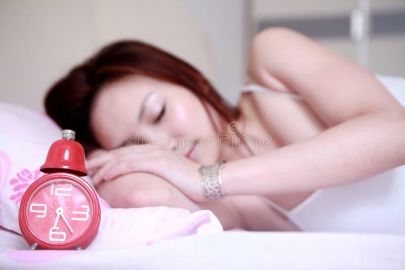 Asiatisches Mädchen, das mit Borduhr schläft stockfoto