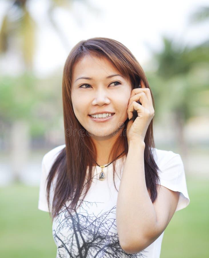 Asiatisches Mädchen, das mit Handy benennt stockfotografie