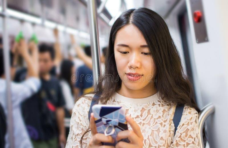 Asiatisches Mädchen, das Telefon auf U-Bahn verwendet lizenzfreie stockfotografie