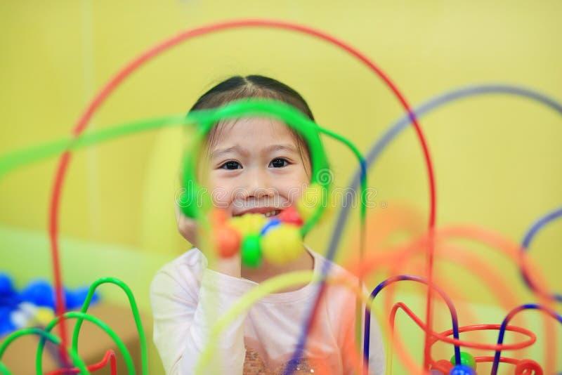 Asiatisches Mädchen der Nahaufnahme Kinder, daspädagogisches Spielzeug für Gehirnentwicklung am Kinderraum spielt stockfotografie