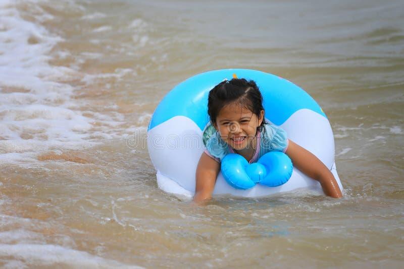 Asiatisches Mädchen in der Schwimmen an der Küste mit einem Lächeln auf glücklichem stockbild