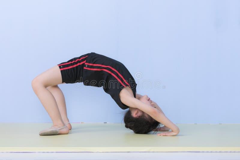 Asiatisches Mädchen in der Sportkleidung, die eine Brückenhaltung aufwirft stockbild