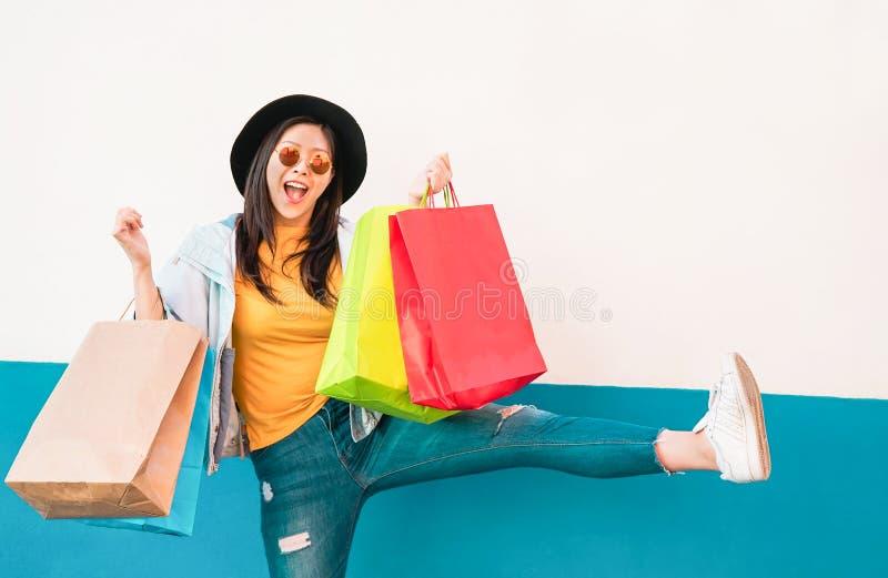 Asiatisches Mädchen der verrückten Mode, welches das Einkaufen in der Mallmitte - glückliche Chinesin hat den Spaß kauft neue Kle stockfoto