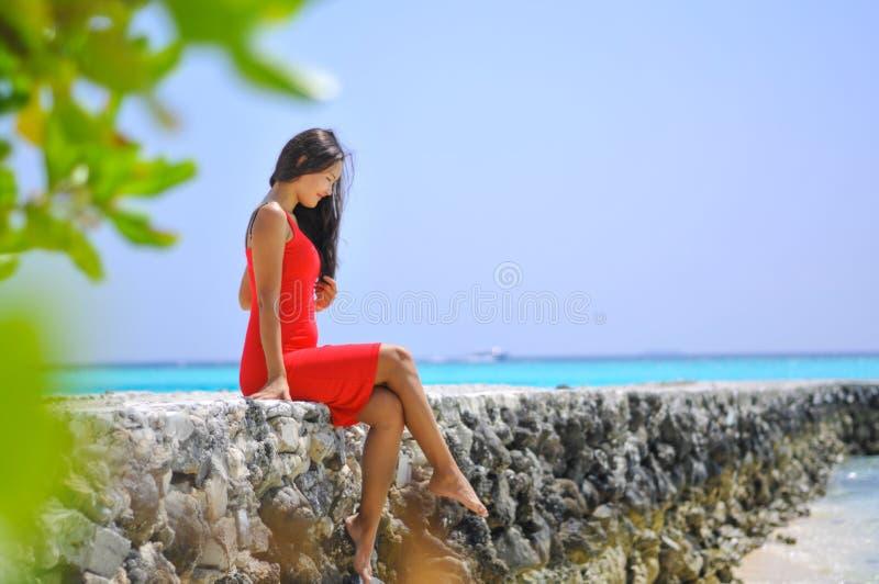 Asiatisches Mädchen in einem roten Kleid auf dem Pier am tropischen Strand stockbild