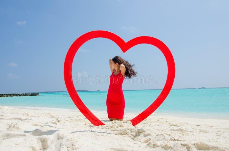 Asiatisches Mädchen in einem roten Kleid, das auf Knien am tropischen Strand innerhalb des Herzens steht stockbilder
