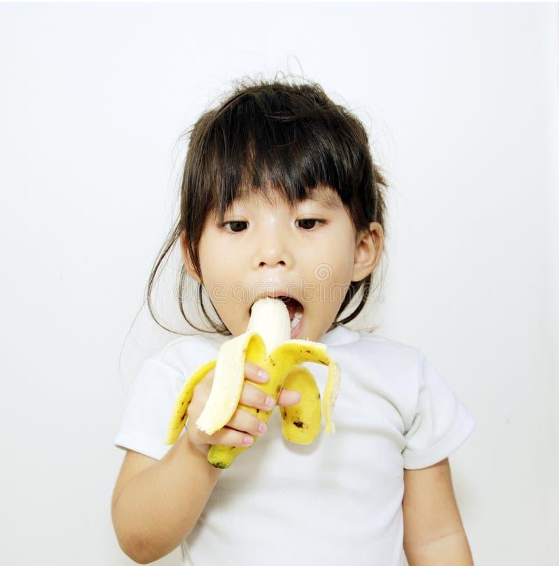 asiatisches Mädchen essen Banane lizenzfreie stockbilder