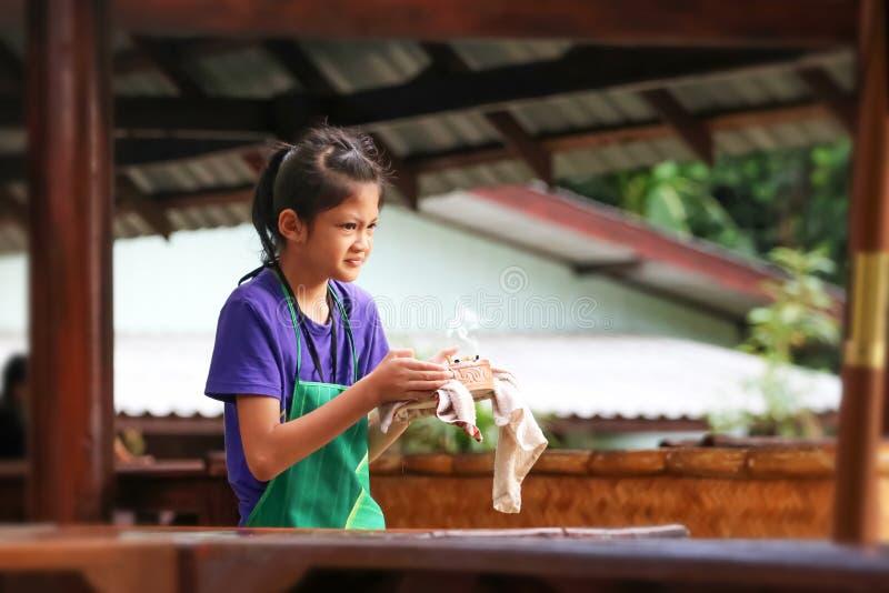 Asiatisches Mädchen fühlte sich beim Halten des Aschenbechers angewidert Kinder, die im Restaurant während des Sommers arbeiten lizenzfreies stockbild