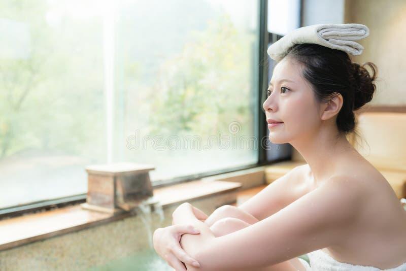 Asiatisches Mädchen genießen die Ansicht, die auf Poolside sitzt lizenzfreie stockfotos