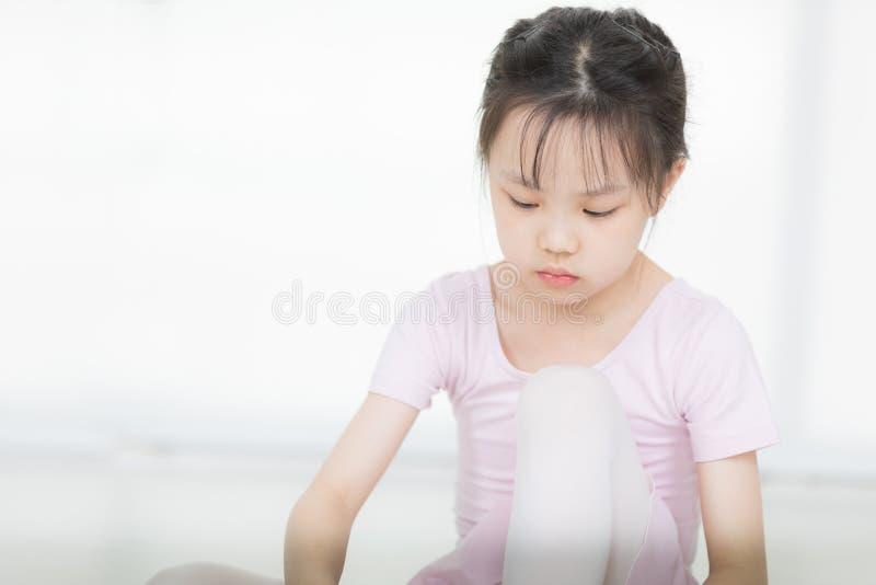 Asiatisches Mädchen im rosa Kleid soll für Ballett sich vorbereiten lizenzfreie stockfotografie