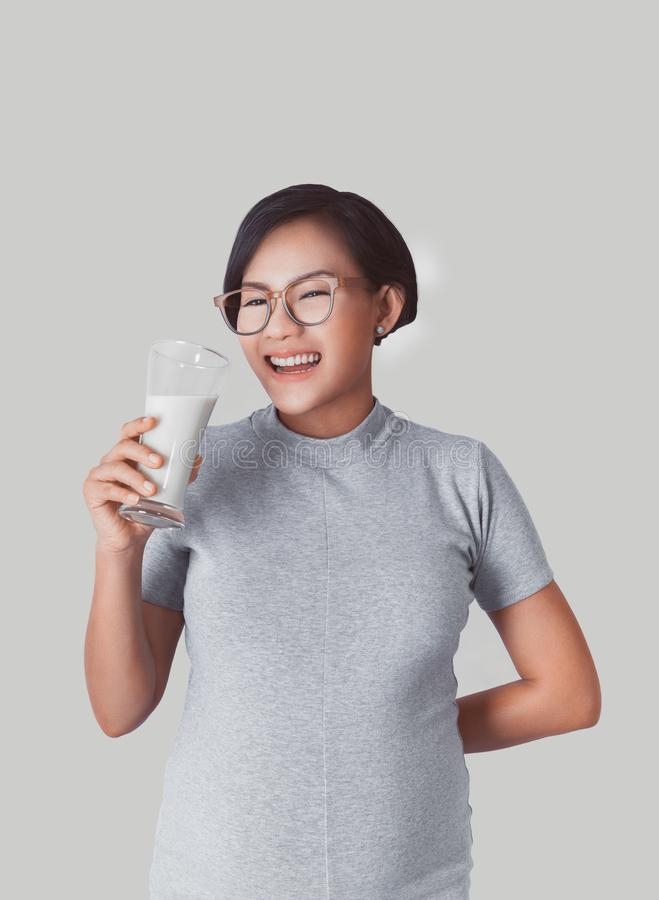 Asiatisches Mädchen lächelt, als sie Trinkmilch war lizenzfreie stockfotografie