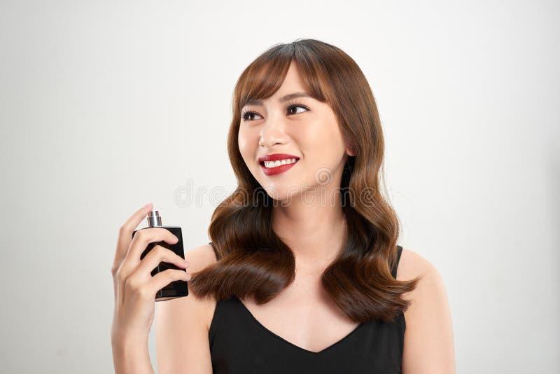Asiatisches Mädchen mit dem Parfüm, junger Frau, die Parfüm auf ihrem Handgelenk und Riechen anwenden lizenzfreies stockbild