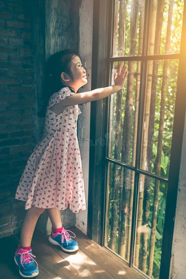 Asiatisches Mädchen mit dem schönen Kleid, welches die Sonnenaufgangstellung betrachtet stockbild