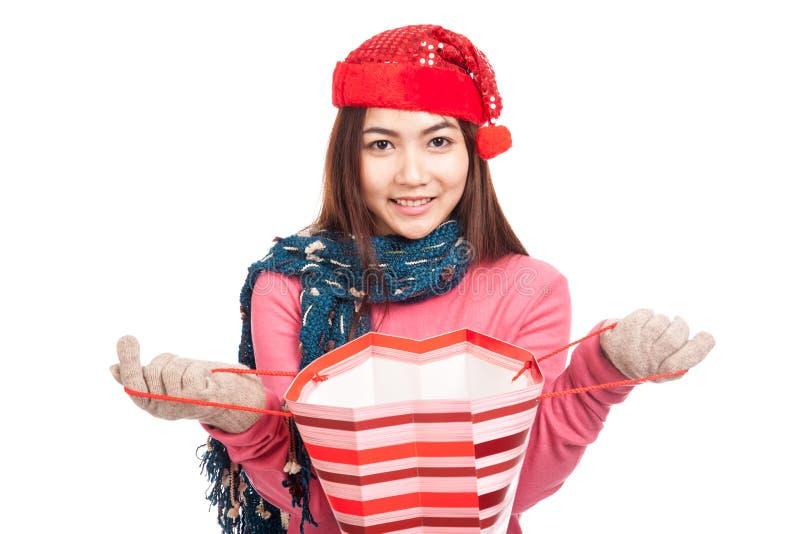 Asiatisches Mädchen mit offener Einkaufstasche des roten Weihnachtshut-Lächelns lizenzfreies stockfoto