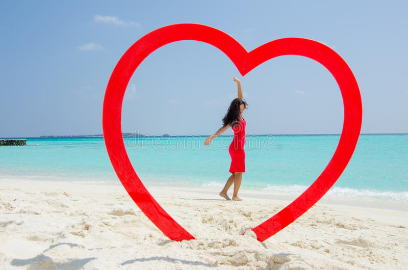 Asiatisches Mädchen in rotes Kleidersteigenden Händen am tropischen Strand innerhalb des Herzens stockfotografie