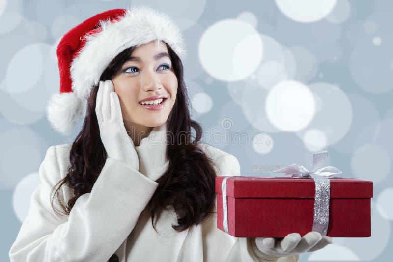 Asiatisches Mädchen in Sankt-Hut, der eine Geschenkbox hält stockfotografie