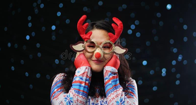 Asiatisches Mädchen-tragende Weihnachtsstrickjacke und Weihnachtsren Glas stockbild