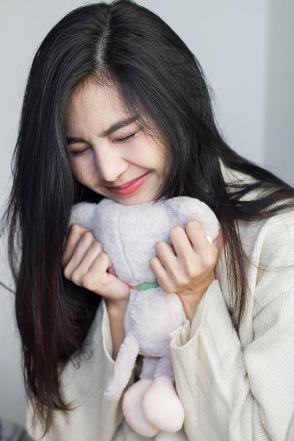 Asiatisches Mädchen umarmen ihre Puppe stockfotografie