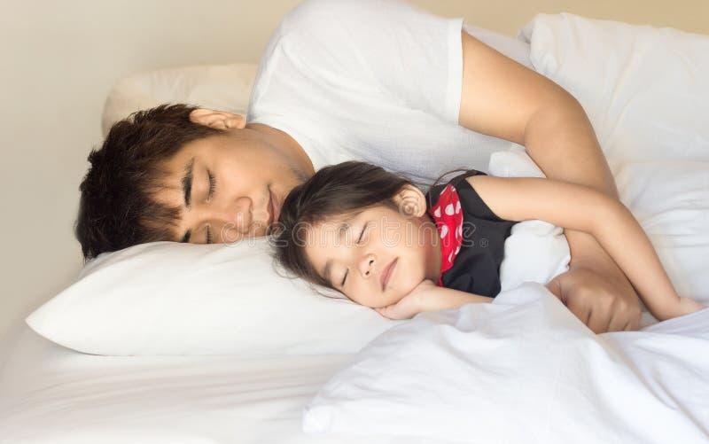 Asiatisches Mädchen und Vater, die auf Bett schläft stockfotografie