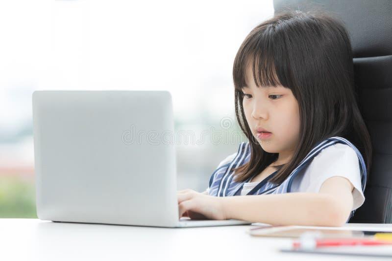 Asiatisches Mädchen verwendet Laptop und Lächeln zur Kamera stockfotografie