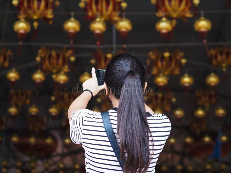 Asiatisches Mädchen, welches Fotografie die Lampe vom Handy nimmt stockfotos