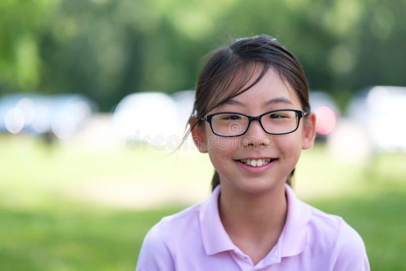 Asiatisches Mädchenporträt, das im Park lächelt lizenzfreies stockbild
