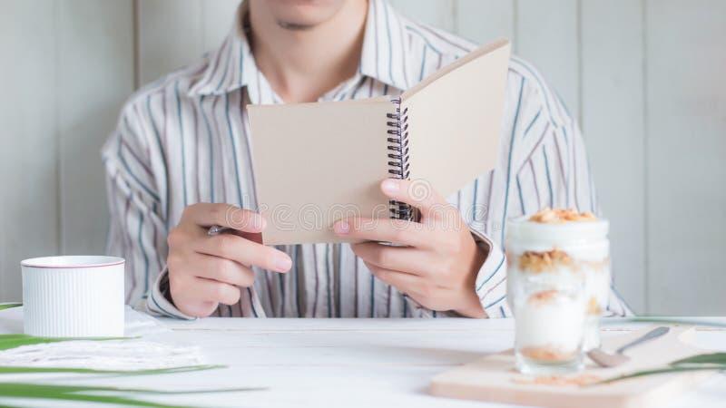 Asiatisches männliches haltenes Notizbuch des ausgewählten Fokus mit gesunder Mahlzeit der Unschärfe machte vom Granola im Glasvo stockfoto
