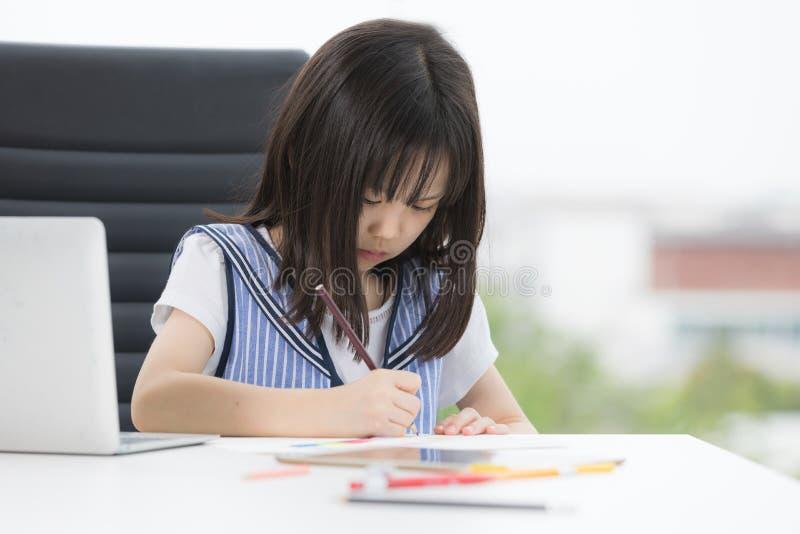 Asiatisches M?dchen zeichnet ernsthaft lizenzfreie stockfotos