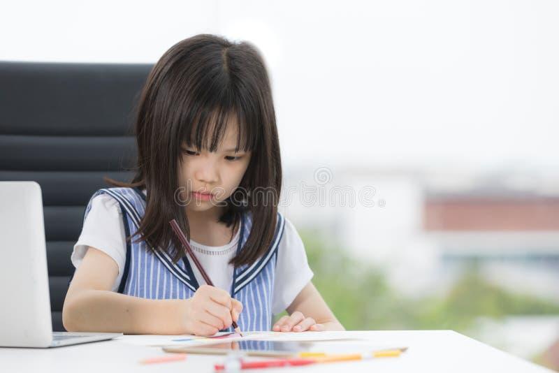 Asiatisches M?dchen zeichnet ernsthaft stockfotografie