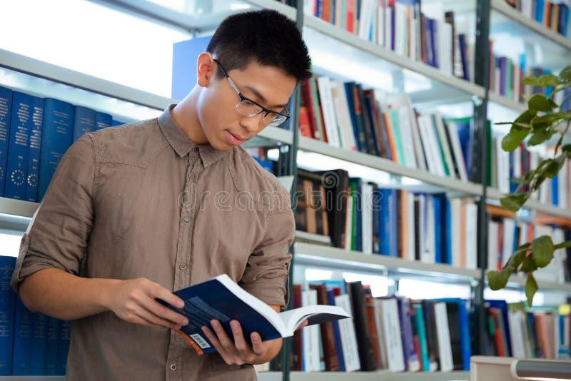 Asiatisches Mannlesebuch in der Bibliothek stockfotos