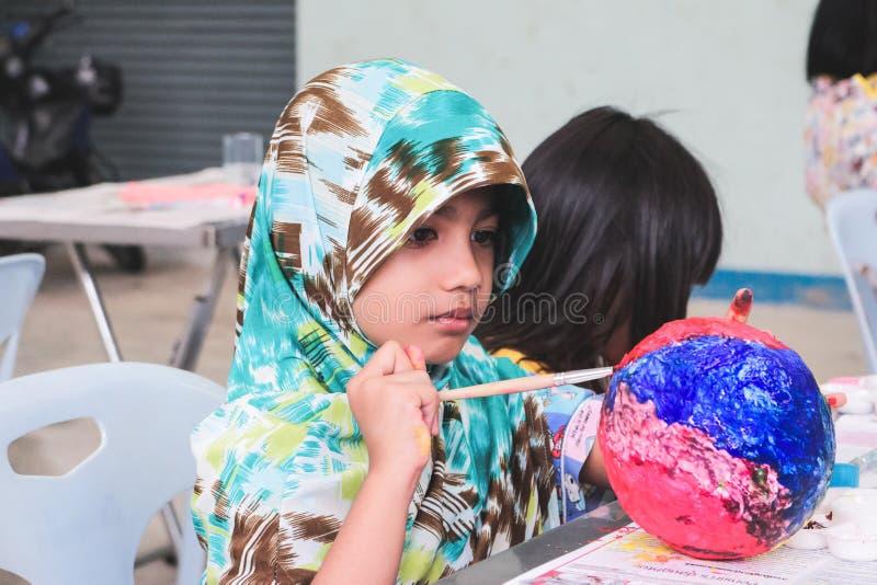 Asiatisches moslemisches Kind malt einen Kunstball stockbild