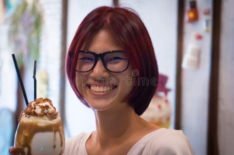 Asiatisches nerdy Mädchen des roten Haares, das Schokoladenerschütterung hat lizenzfreies stockfoto