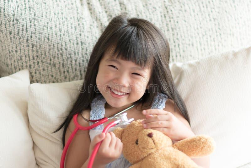 Asiatisches nettes kleines Mädchen ist lächelnd spielend und Doktor mit stetho lizenzfreie stockfotos