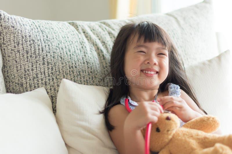 Asiatisches nettes kleines Mädchen ist lächelnd spielend und Doktor mit stetho lizenzfreie stockfotografie