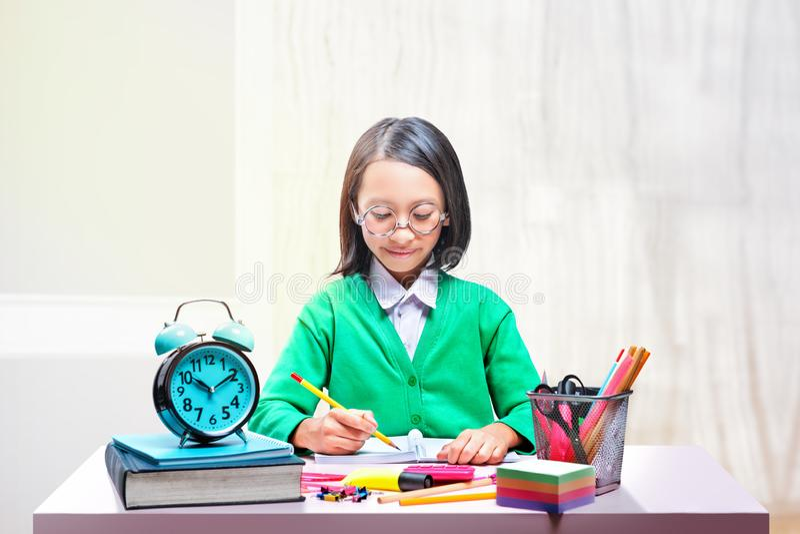 Asiatisches nettes Mädchen in den Gläsern lernend mit der Schule stationär auf dem Schreibtisch lizenzfreies stockbild