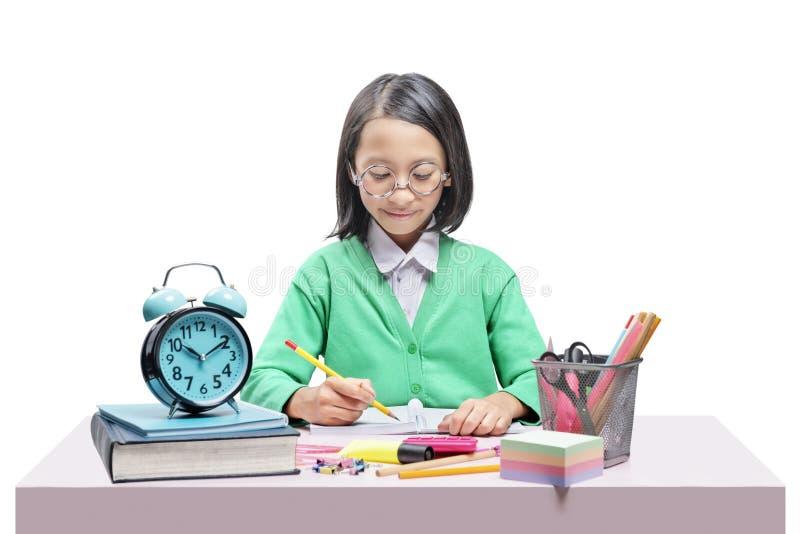 Asiatisches nettes Mädchen in den Gläsern lernend mit der Schule stationär auf dem Schreibtisch lizenzfreie stockfotos
