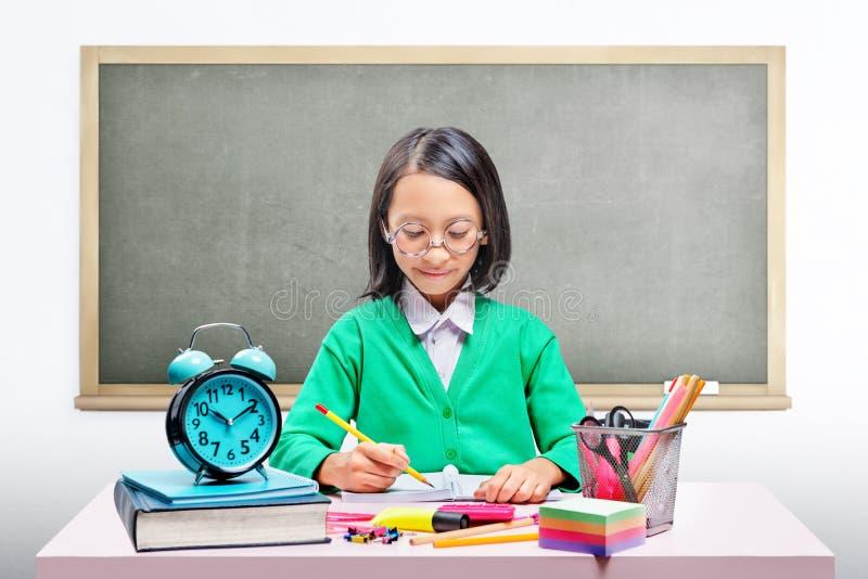 Asiatisches nettes Mädchen in den Gläsern lernend mit der Schule stationär auf dem Schreibtisch stockfotografie