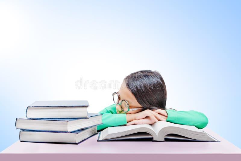 Asiatisches nettes Mädchen mit Gläsern schlafen auf Buch auf dem Schreibtisch ein stockfoto