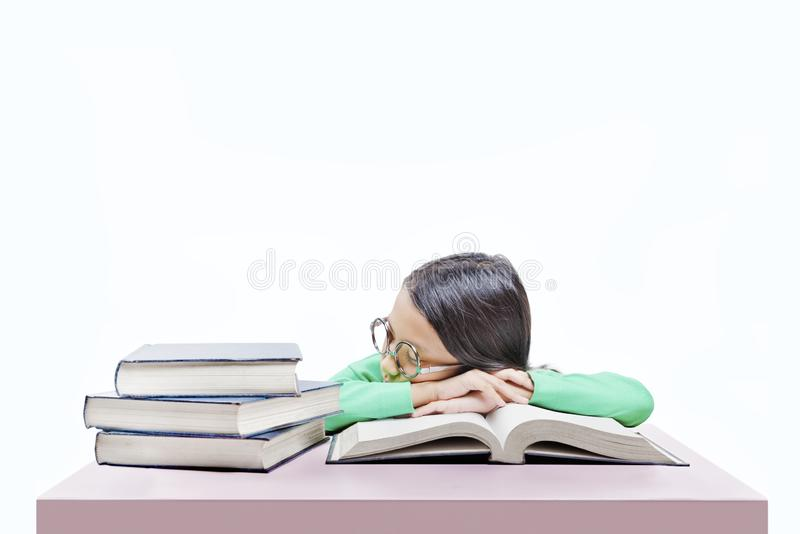 Asiatisches nettes Mädchen mit Gläsern schlafen auf Buch auf dem Schreibtisch ein lizenzfreie stockfotos