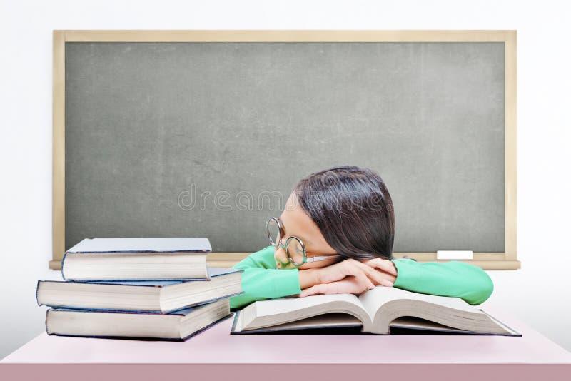 Asiatisches nettes Mädchen mit Gläsern schlafen auf Buch auf dem Schreibtisch ein stockbild