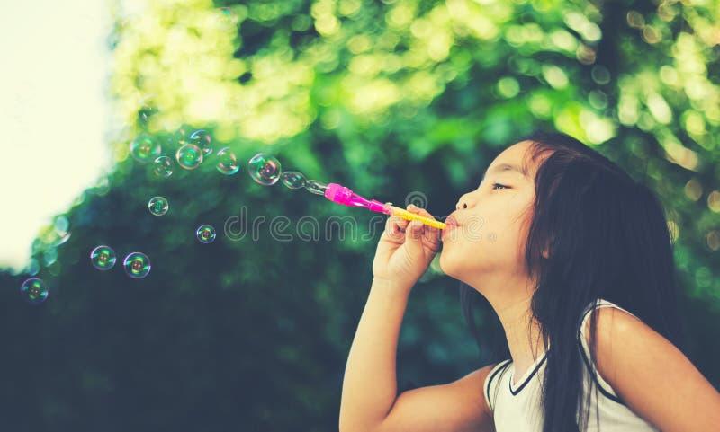 Asiatisches nettes Mädchen playling Schlag sprudelt zusammen am Feld lizenzfreies stockfoto