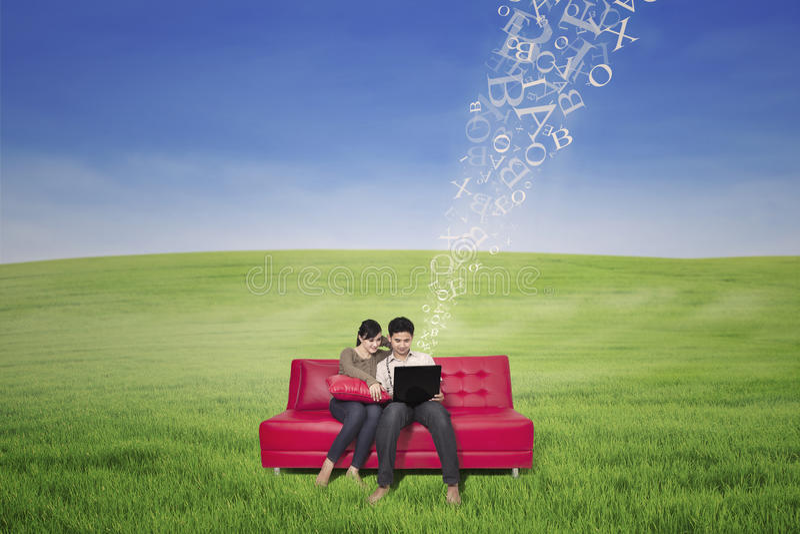 Asiatisches Paar unter Verwendung des Laptops mit Fliegen beschriftet im Freien lizenzfreie stockfotografie